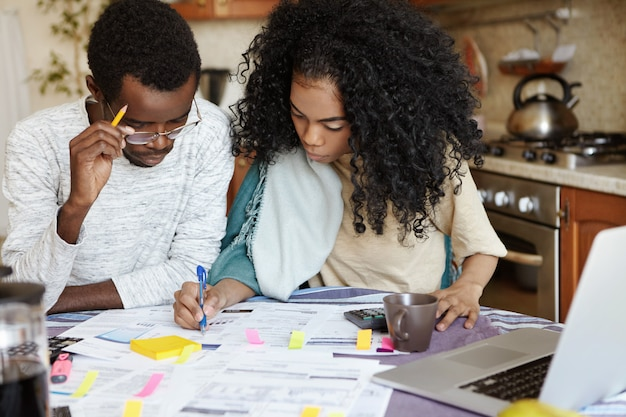 Young confident african housewife with afro hairstyle helping her husband to manage domestic finances, calculating and making notes with pen, both sitting at kitchen table with laptop and papers Free Photo