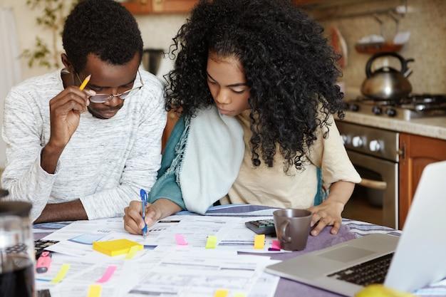 ノートパソコンと紙で台所のテーブルに座って、夫が家計を管理し、計算してペンでメモを書くのを助けるアフロの髪型を持つ自信を持って若いアフリカの主婦 無料写真