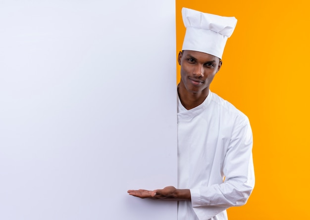 Young confident afro-american cook in chef uniform stands behind white wall and holds hand straight isolated on orange background with copy space Free Photo