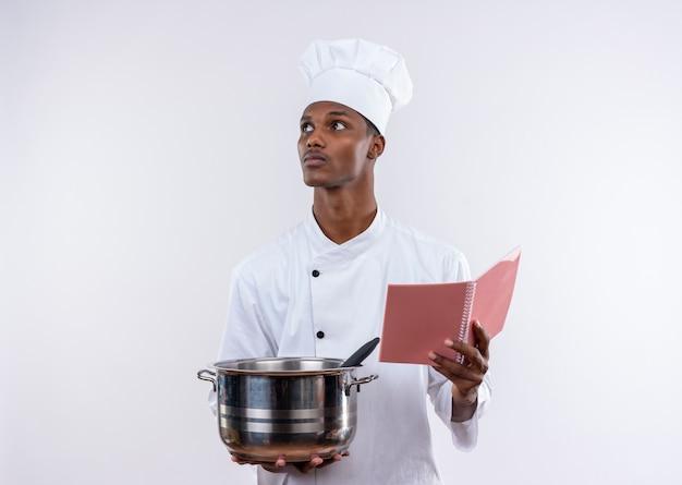 シェフの制服を着た若い自信を持ってアフリカ系アメリカ人の料理人は、コピースペースと孤立した白い背景で横に見ている鍋とノートブックを保持します 無料写真