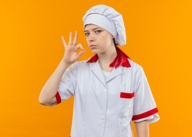 シェフの制服のジェスチャーで若い自信を持って金髪の女性シェフは、オレンジ色の壁に孤立しているように見えます。 無料写真