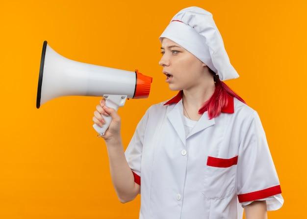 シェフの制服を着た若い自信を持って金髪の女性シェフがスピーカーから叫び、オレンジ色の壁に隔離された側を見ます 無料写真