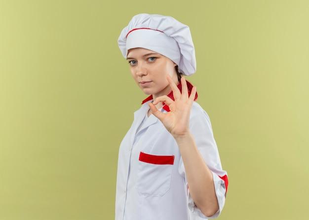 シェフの制服を着た若い自信を持って金髪の女性シェフが横に立って、緑の壁に隔離された手振りでok 無料写真