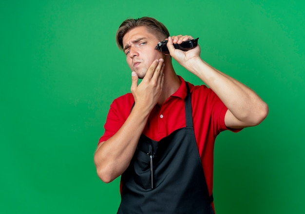 Young confident blonde male barber in uniform holds face trimming beard with hair clipper isolated on green space with copy space Free Photo