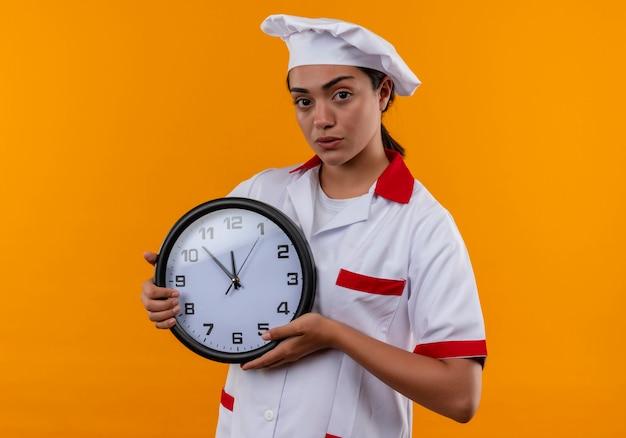 La giovane ragazza caucasica sicura del cuoco in uniforme del cuoco unico tiene l'orologio con entrambe le mani isolate sulla parete arancione Foto Gratuite