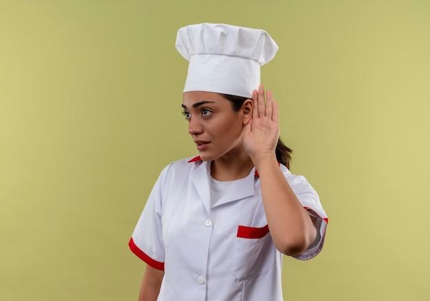 シェフの制服のジェスチャーで若い自信を持って白人料理人の女の子は、コピースペースで緑の壁に分離されたサインを聞くことができません 無料写真