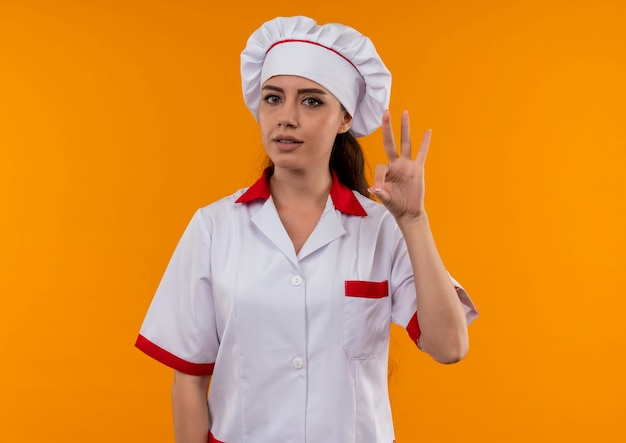 シェフの制服のジェスチャーで若い自信を持って白人料理人の女の子はコピースペースでオレンジ色の壁に分離された手のサインok 無料写真