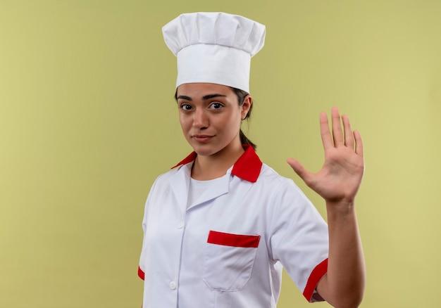 シェフの制服のジェスチャーで若い自信を持って白人料理人の女の子は、コピースペースで緑の壁に分離された手のサインを停止します 無料写真