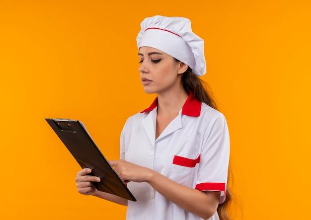 シェフの制服を着た若い自信を持って白人料理人の女の子は、コピースペースでオレンジ色の壁に分離されたクリップボードを保持し、見ています 無料写真