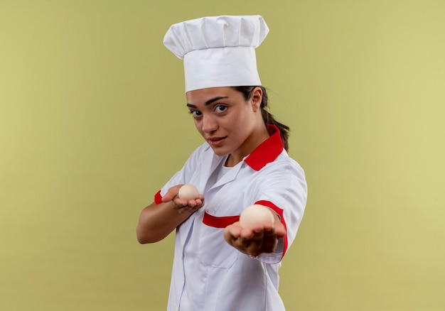 シェフの制服を着た若い自信を持って白人料理人の女の子は、コピースペースで緑の壁に隔離された卵を保持します 無料写真