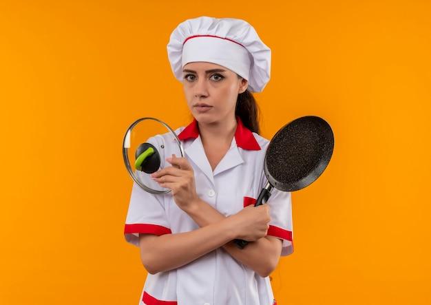 シェフの制服を着た若い自信を持って白人料理人の女の子は、コピースペースでオレンジ色の壁に分離されたフライパンと蓋を保持します 無料写真