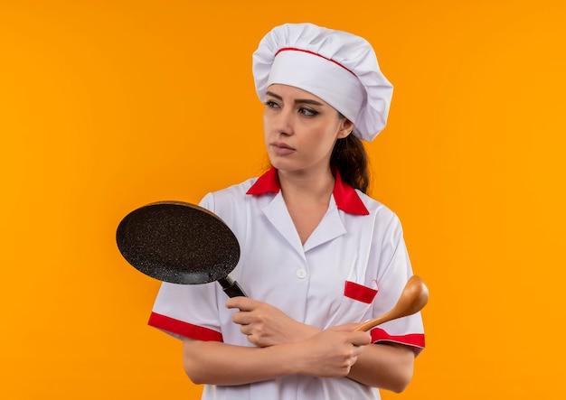シェフの制服を着た若い自信を持って白人料理人の女の子は、コピースペースでオレンジ色の壁に分離されたフライパンと木のスプーンを保持します 無料写真