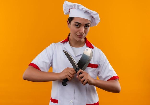シェフの制服を着た若い自信を持って白人料理人の女の子は、コピースペースでオレンジ色の壁に分離されたナイフを保持します 無料写真