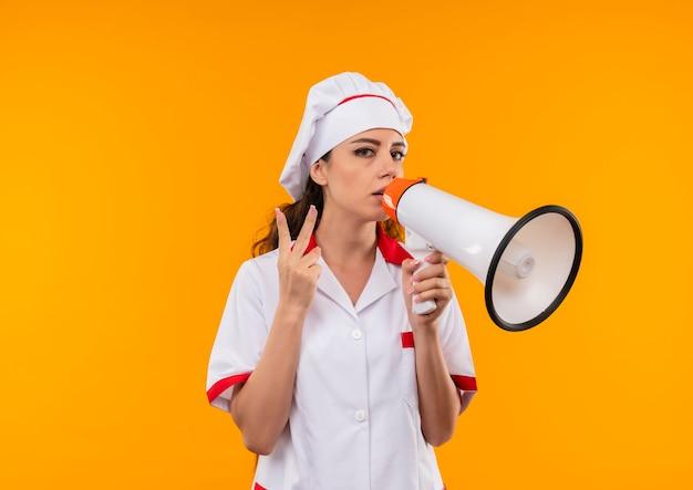 シェフの制服を着た若い自信を持って白人料理人の女の子は大きなスピーカーを保持し、コピースペースでオレンジ色の壁に分離された勝利の手のサインをジェスチャーします 無料写真