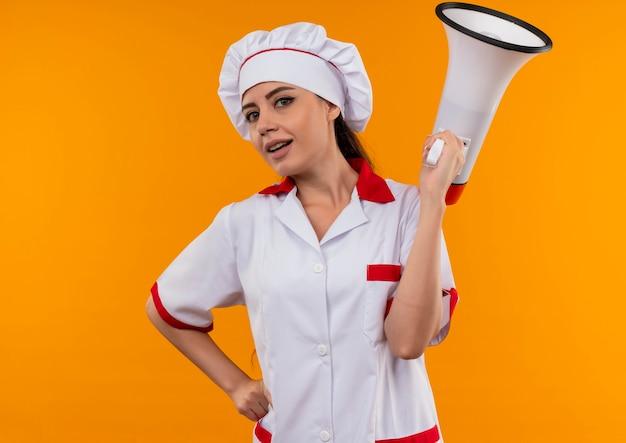 シェフの制服を着た若い自信を持って白人料理人の女の子は、コピースペースでオレンジ色の壁に隔離されたスピーカーを保持します 無料写真
