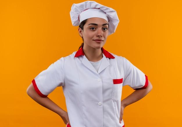 シェフの制服を着た若い自信を持って白人料理人の女の子は、コピースペースでオレンジ色の壁に隔離された腰に手を置きます 無料写真