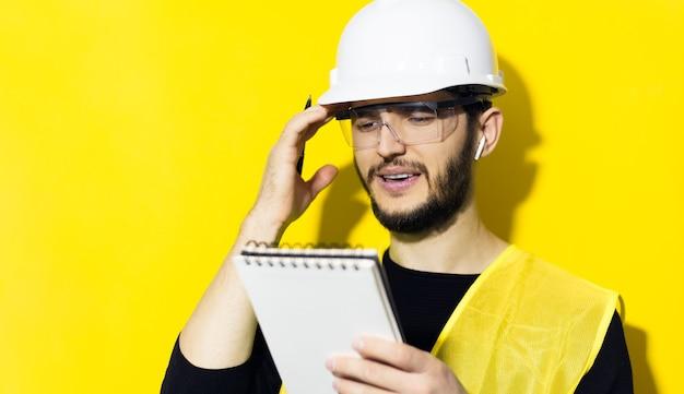 자신감이 젊은이, 작성기 엔지니어 노트북에 쓰기, 무선 이어폰을 사용하고, 노란색 벽에 건설을 위해 안전 헬멧과 고글을 착용합니다. 프리미엄 사진