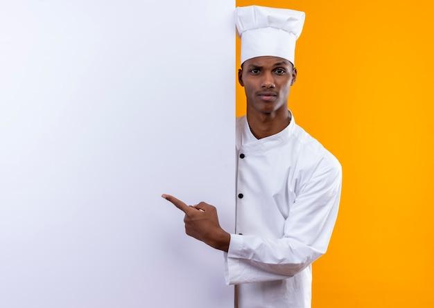 シェフの制服を着た若い混乱したアフリカ系アメリカ人の料理人は、白い壁の後ろに立って、オレンジ色の壁に隔離された壁を指しています 無料写真