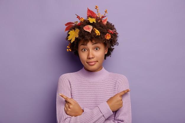 La giovane donna afro confusa indica lateralmente, sceglie tra due opzioni, chiede di aiutare a prendere una decisione, indica destra e sinistra, ha foglie autunnali e bacche nei capelli ricci, isolate sul muro viola Foto Gratuite