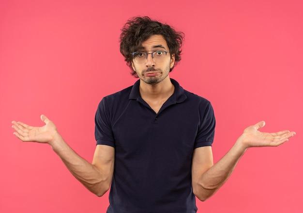 光学ガラスの黒いシャツを着た若い混乱した男は唇を財布し、ピンクの壁に隔離された手を開いたままにします 無料写真