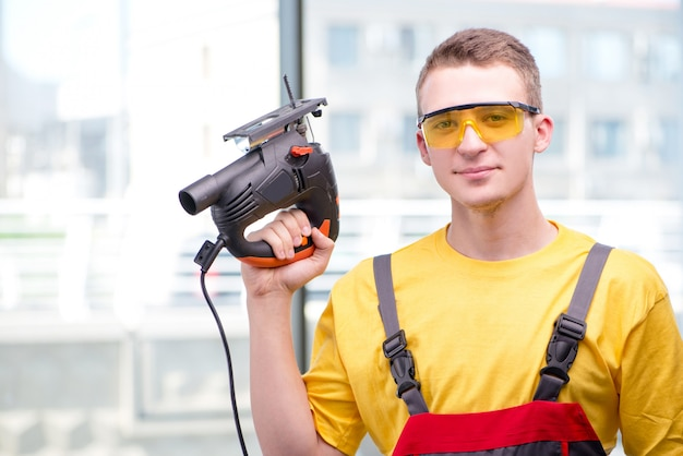 Young construction worker in yellow coveralls Premium Photo