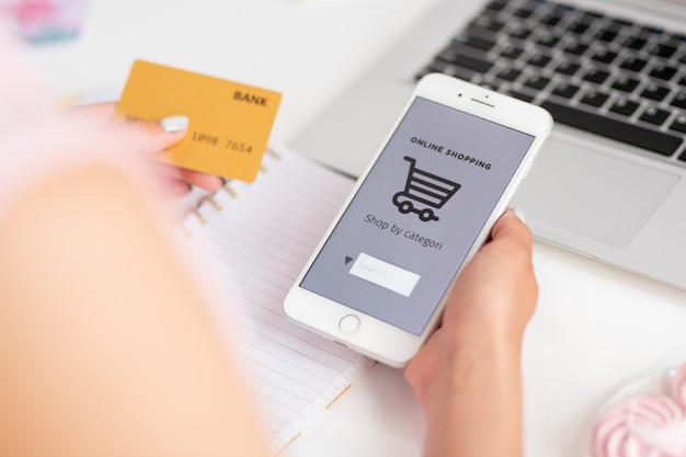 Молодой покупатель интернет-магазина со смартфоном и банковской картой ищет товары в сети, собираясь сделать заказ Premium Фотографии