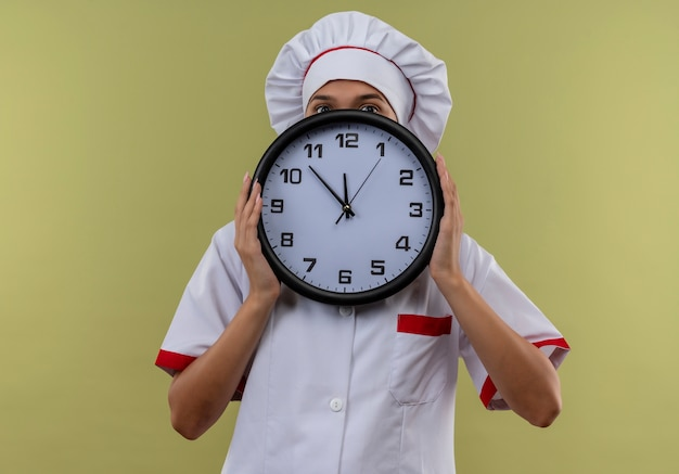 Giovane cuoco femmina che indossa uniforme da chef coperto faccia con orologio da parete sul muro verde isolato Foto Gratuite
