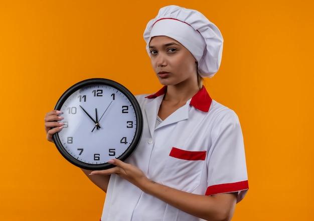 Giovane cuoco femmina che indossa uniforme chef azienda orologio da parete sulla parete arancione isolata Foto Gratuite