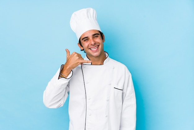 Young cook man isolated showing a mobile phone call gesture with fingers. Premium Photo