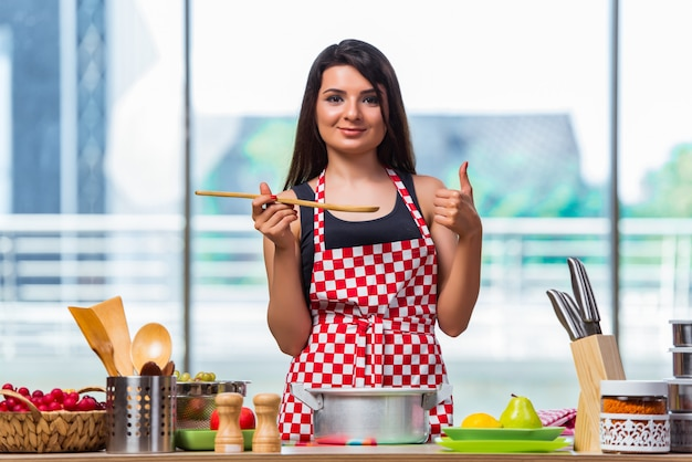 Young cook preparing soup in the kitchen Premium Photo