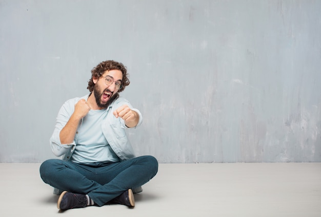 Young cool bearded man sitting on the floor. grunge wall background Premium Photo