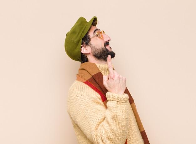 若いクールなひげを生やした男が元気に楽しく笑って、スペースをコピーする片手で上向き Premium写真