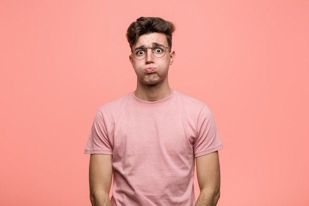 Young cool caucasian man blows cheeks, has tired expression. facial expression . Premium Photo