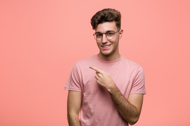 Young cool caucasian man smiling and pointing aside, showing something at blank space. Premium Photo