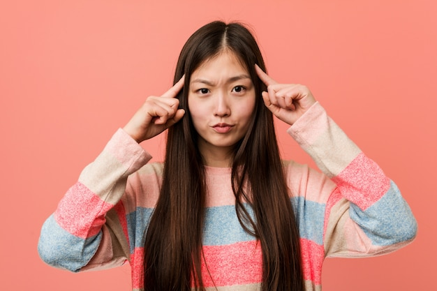 Young cool chinese woman focused on a task, keeping him forefingers pointing head. Premium Photo
