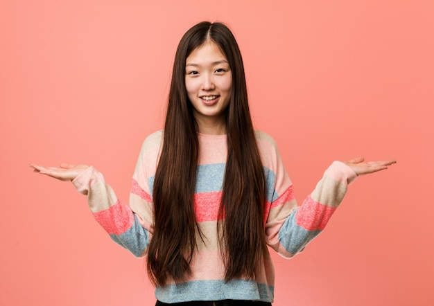 Young cool chinese woman makes scale with arms, feels happy and confident. Premium Photo