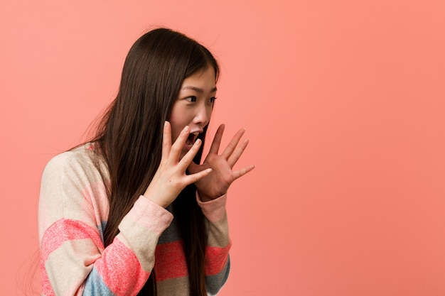 Young cool chinese woman shouts loud, keeps eyes opened and hands tense. Premium Photo