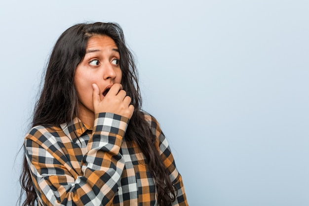 Young cool indian woman thoughtful looking to a copy space covering mouth with hand. Premium Photo