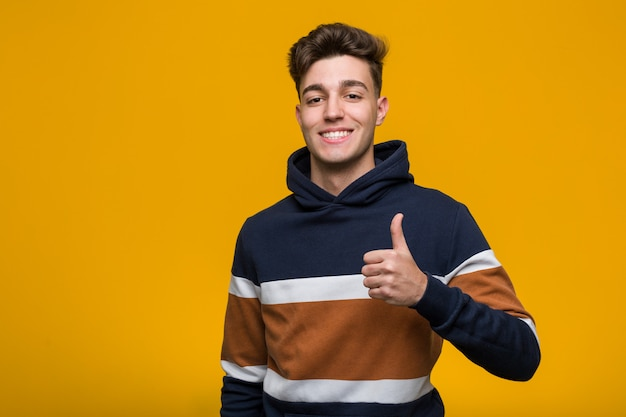 Young cool man wearing a hoodie smiling and raising thumb up Premium Photo