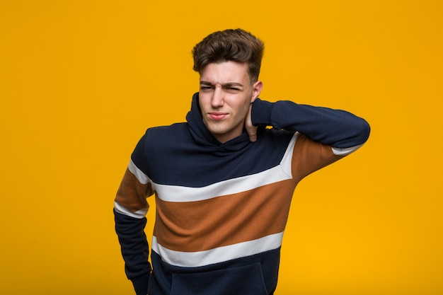 Young cool man wearing a hoodie suffering neck pain due to sedentary lifestyle. Premium Photo