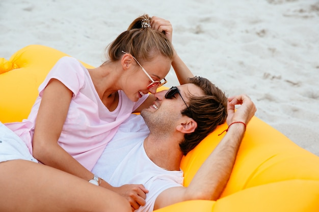 Young couple admire while looking to each other, laying on yellow air sofa lamzac Free Photo