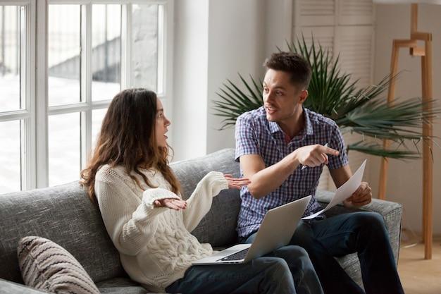 Молодая пара спорит о высоких счетах с ноутбуком и документами Бесплатные Фотографии