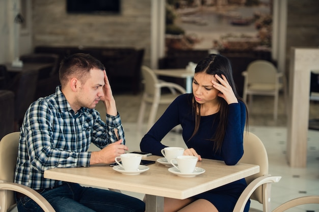 Young couple arguing in a cafe. she's had enough, boyfriend is apologizing. relationship problems. P
