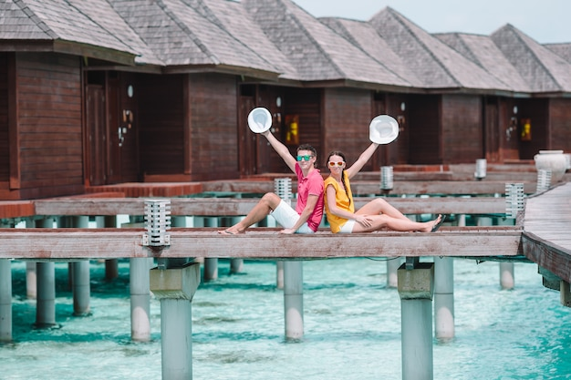 Young couple on beach jetty at tropical island in honeymoon Premium Photo