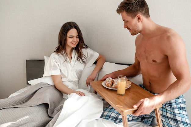 Young couple in the bed. beautiful man is holding the table with delicious breakfast for his sweetheart Premium Photo