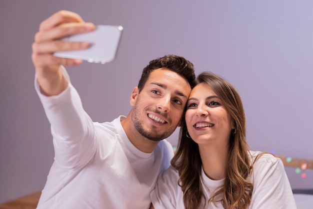 Young couple in bed taking selfie Free Photo