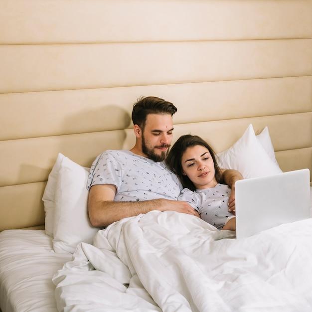 Giovane coppia a letto usando il portatile Foto Gratuite