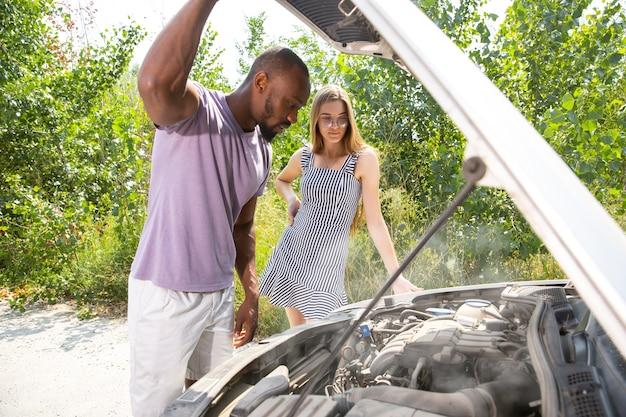 Молодая пара сломала машину во время путешествия Бесплатные Фотографии