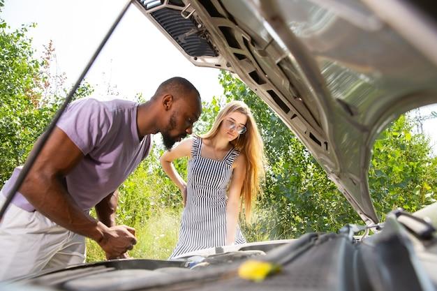 若いカップルが旅行中に車を壊した 無料写真