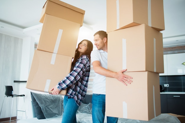 Young couple carrying many cardboard boxes one by one at new home. moving house. Premium Photo